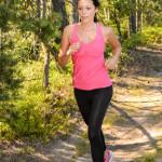 Image of Female Runner in woods with earphones