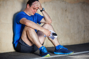 Image of runner sitting against a wall to demonstrate runner's block