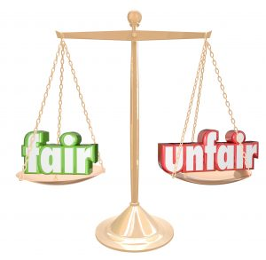 Life isn;t fair illustrated by the words Fair and Unfair on a balance scale